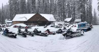 Snowmobiles and fresh snow cover the mountain